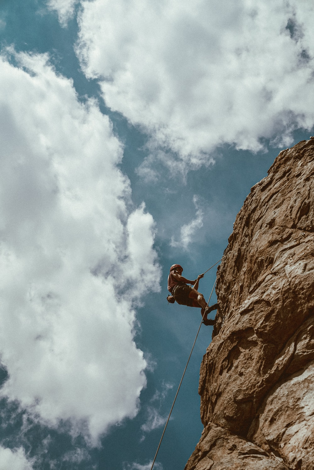 man in red jacket climbing on brown rock mountain under blue and white sunny cloudy sky