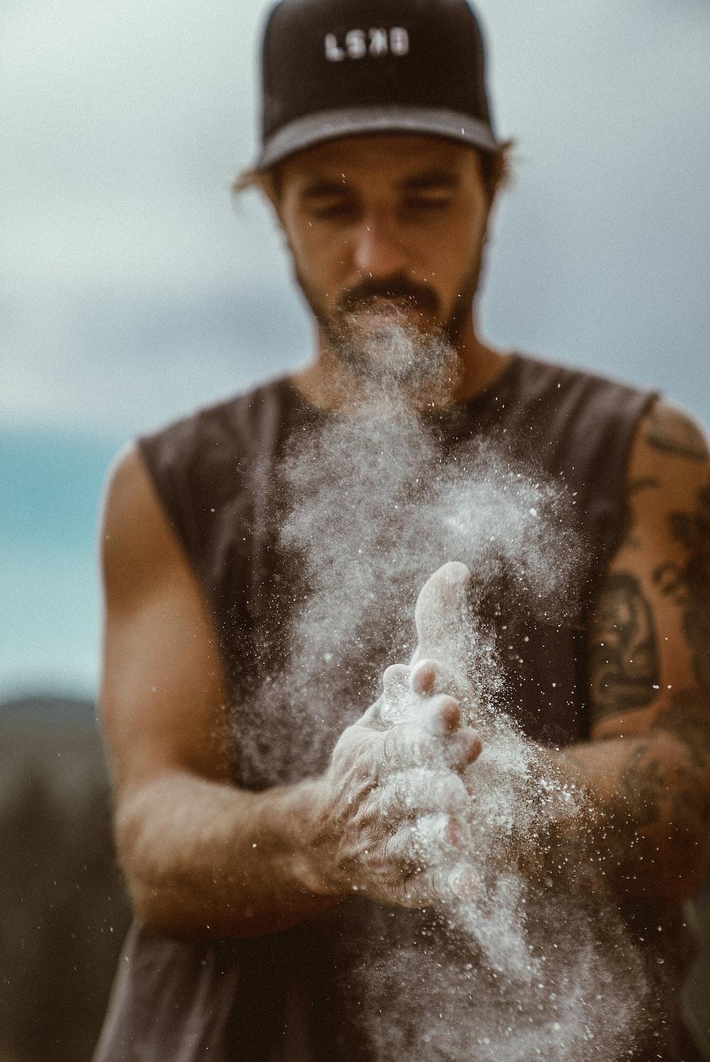 man in black tank top blowing white powder