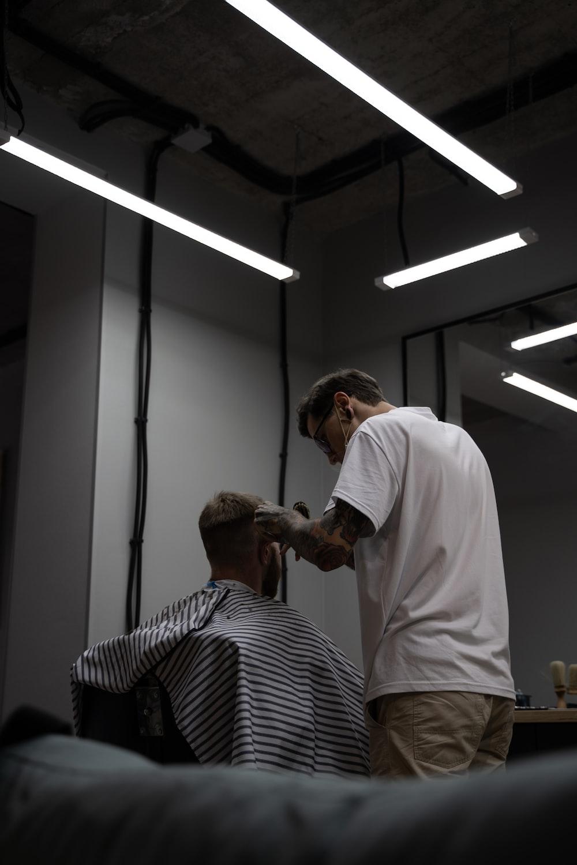 man in white shirt cutting hair of man in black and white stripe shirt