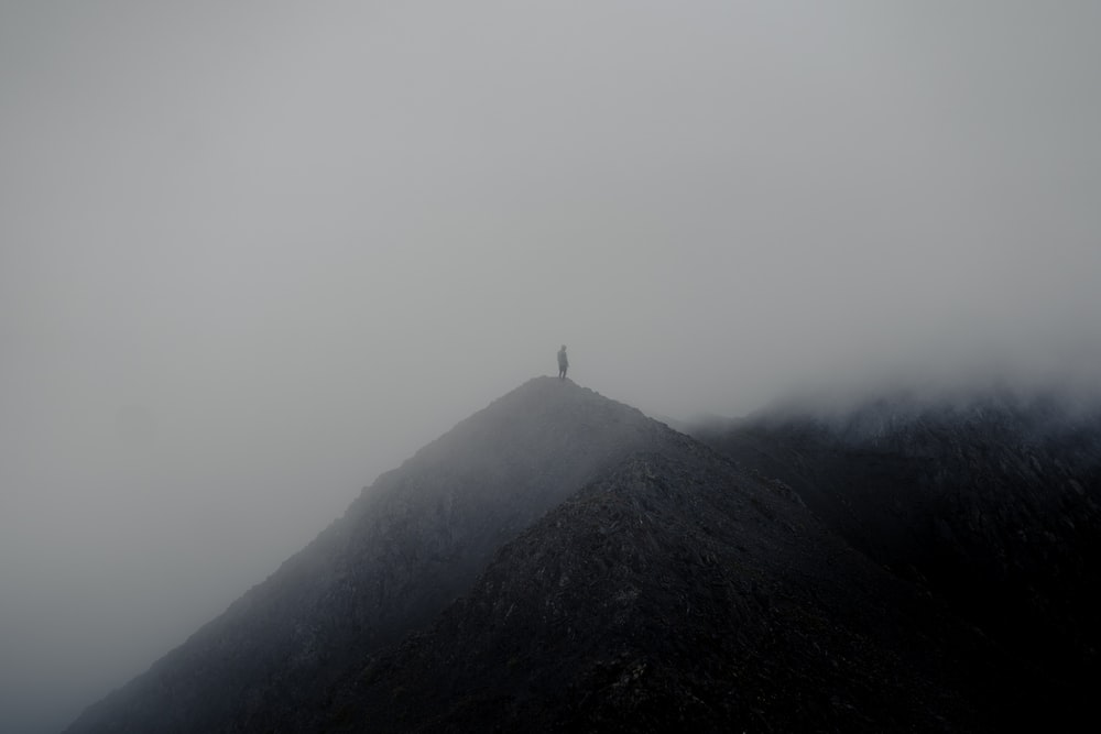 silhouette of person standing on top of mountain during foggy day