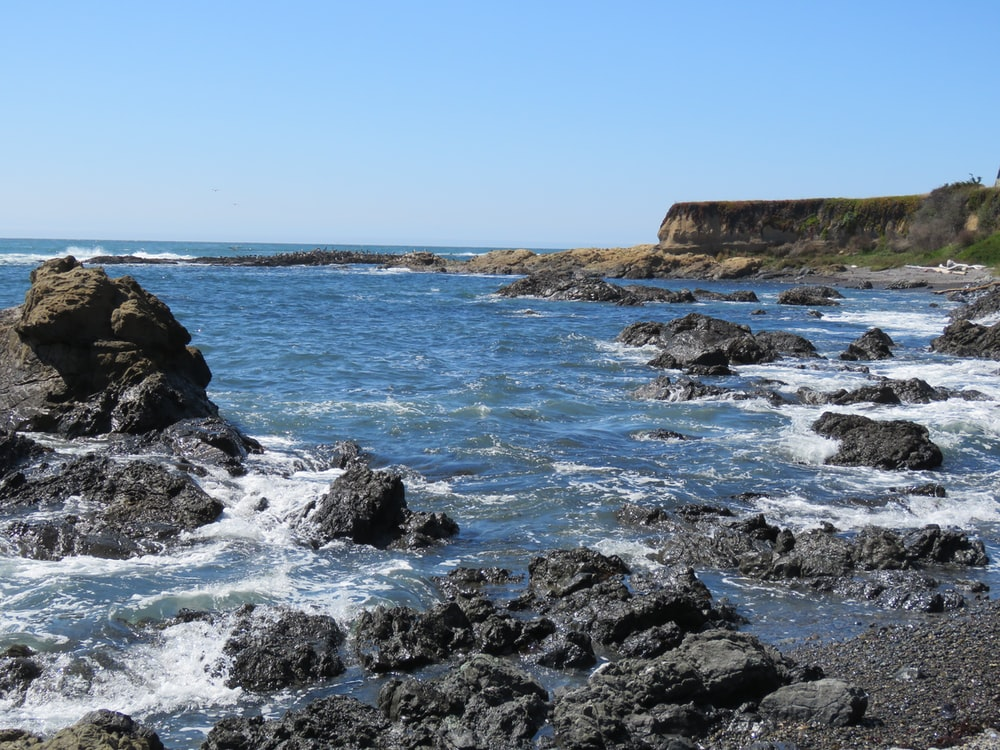 brown rocky mountain beside sea under blue sky during daytime