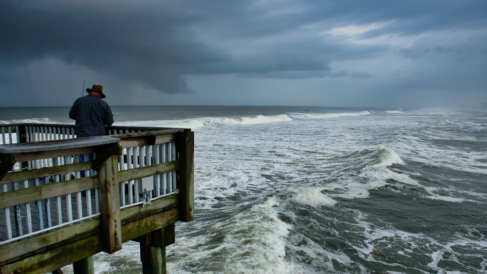 person in black jacket sitting on brown wooden dock over sea waves during daytime