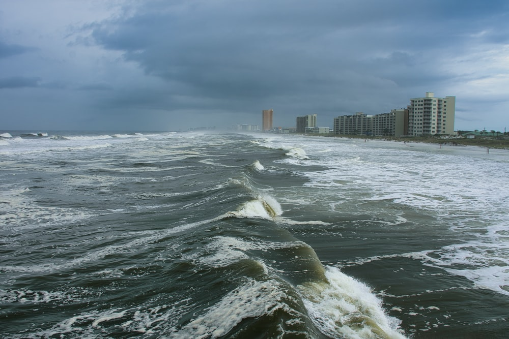 ocean waves near city buildings during daytime