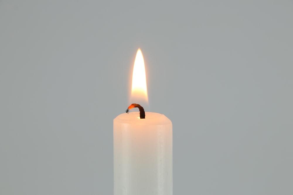 white pillar candle on white surface