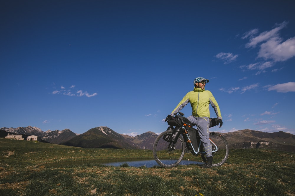 man in yellow jacket riding bicycle on dirt road during daytime