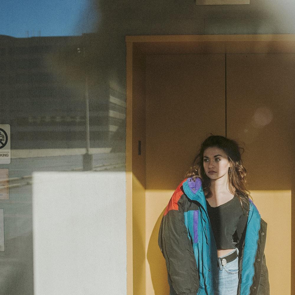 woman in blue jacket standing near brown wooden door