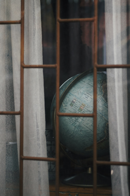 black desk globe on brown wooden shelf