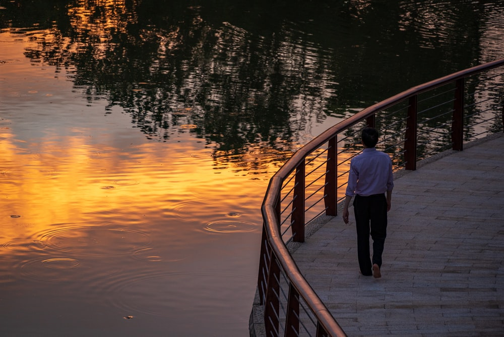 man and woman standing on wooden bridge during sunset