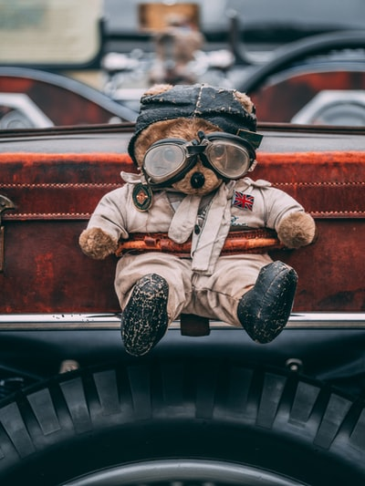 man in brown and white suit wearing goggles sitting on car