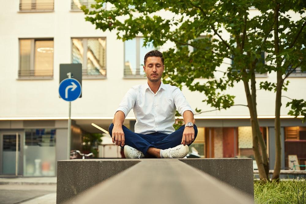 man in white dress shirt sitting on gray concrete bench during daytime
