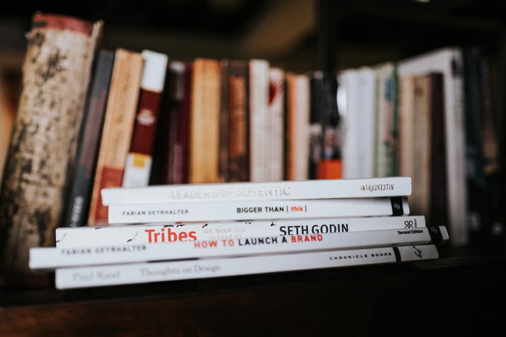 white and red books on brown wooden shelf