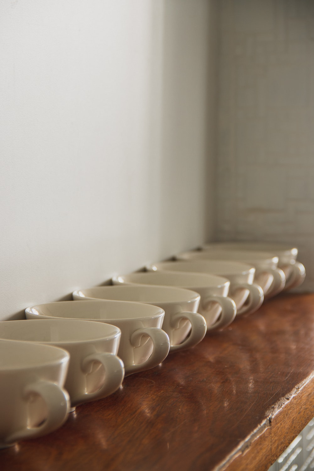 white ceramic mugs on brown wooden table