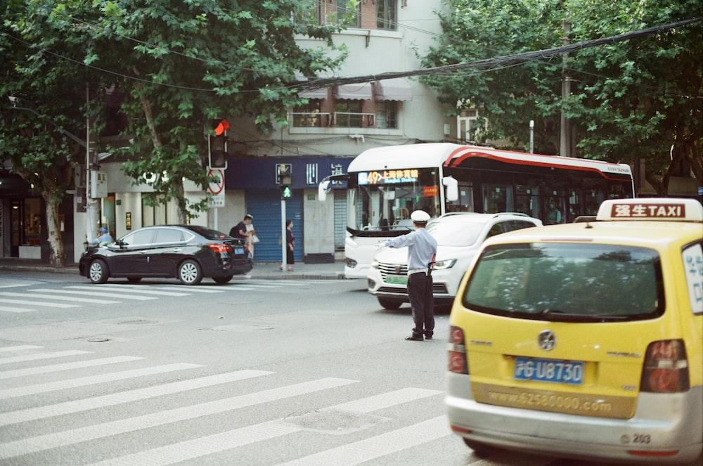 man in white long sleeve shirt standing beside yellow car during daytime