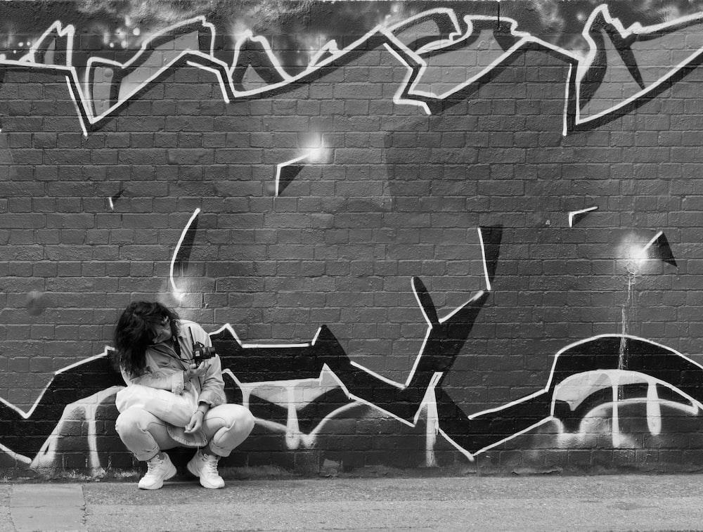 girl sitting on bench near wall with graffiti