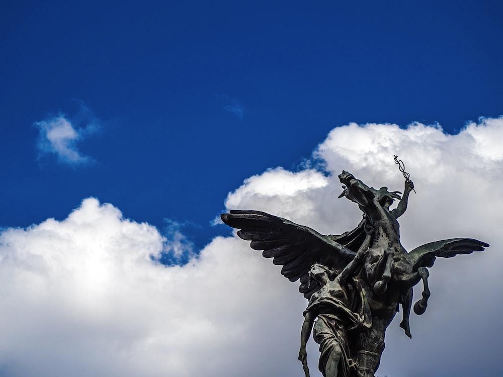 black angel statue under blue sky during daytime