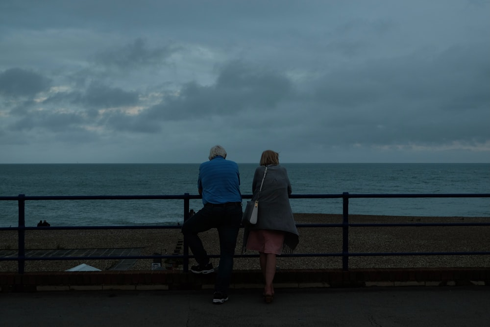 couple sitting on bench near sea during daytime