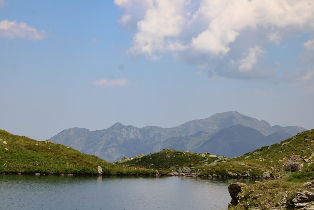 green mountains beside body of water under white clouds during daytime