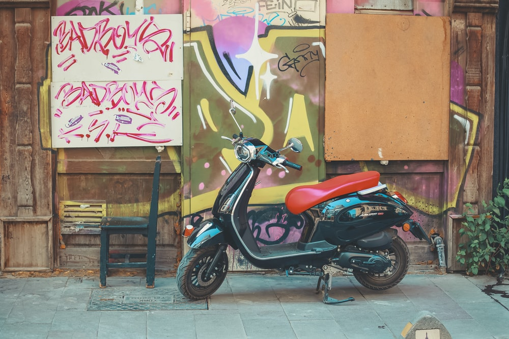 red and black motorcycle parked beside brown wooden fence