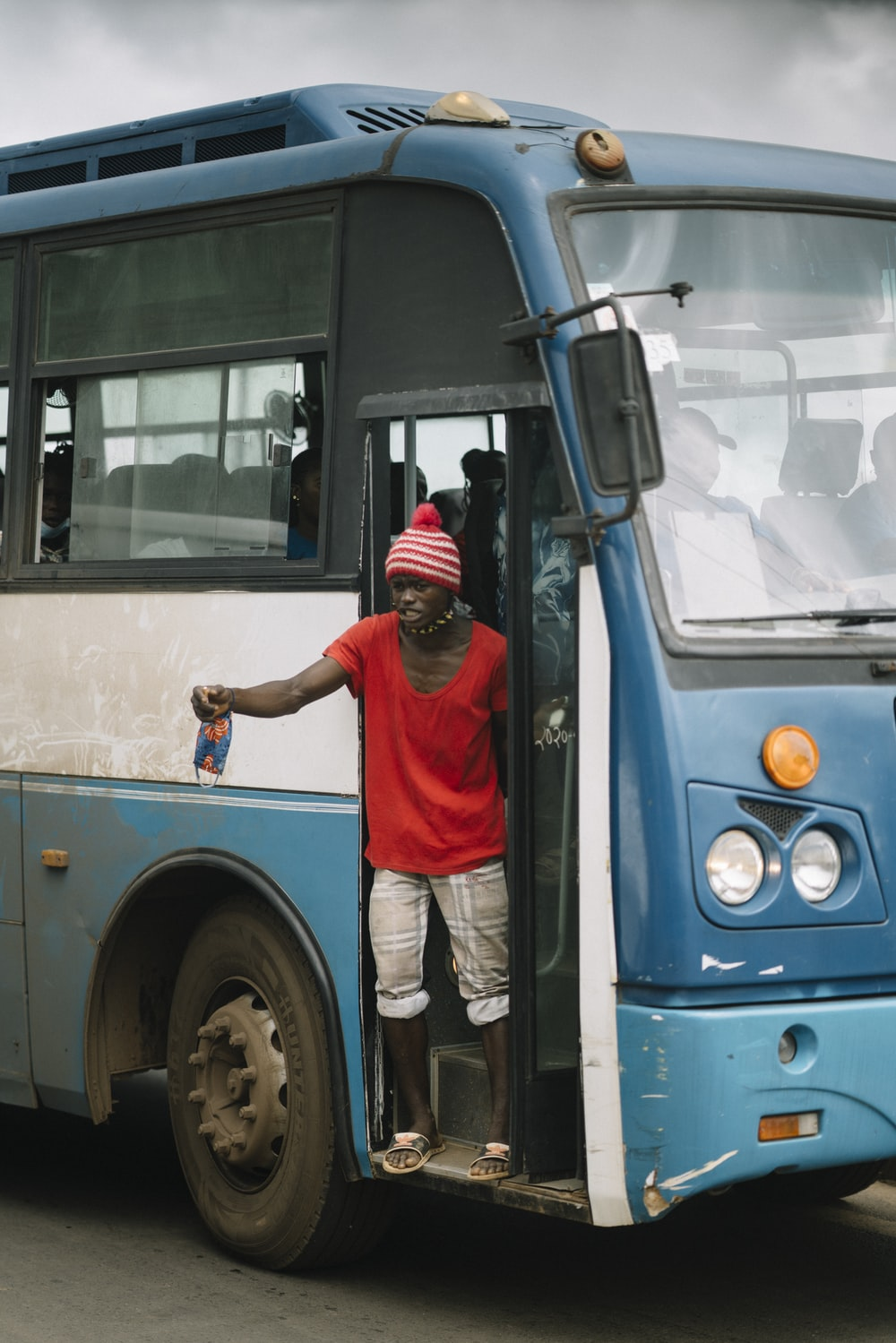 man in red t-shirt and white pants standing in front of blue bus during daytime
