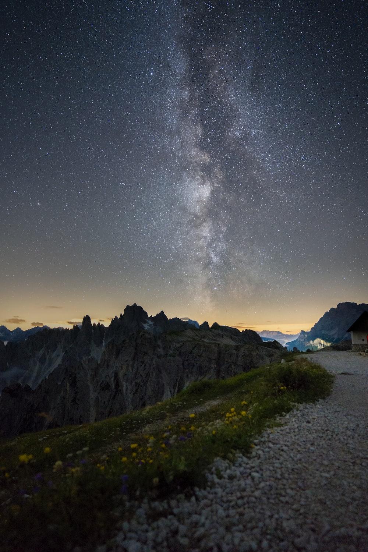 green grass field near mountain under starry night