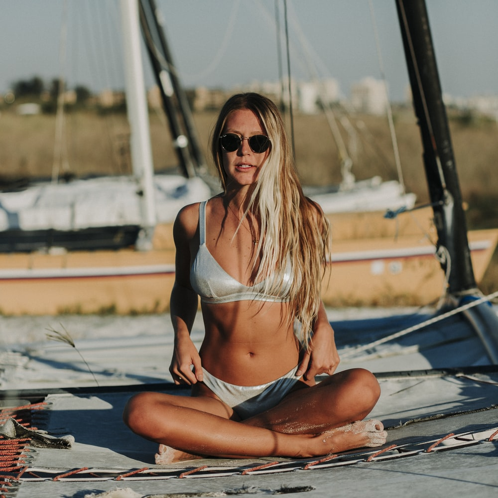 woman in black bikini sitting on blue and white boat during daytime
