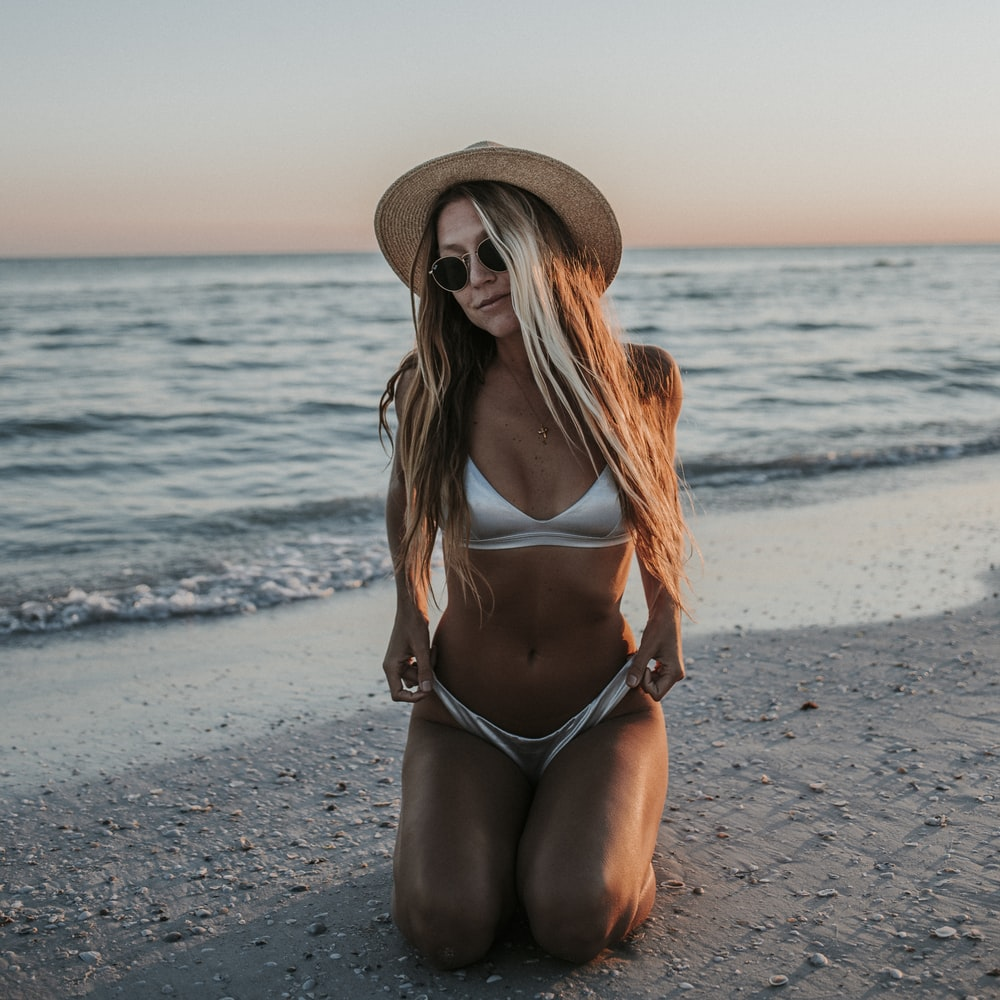 woman in brown sun hat and black bikini bottom sitting on beach shore during daytime