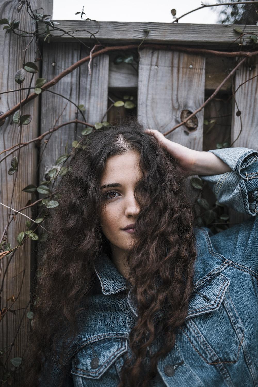 woman in blue denim jacket standing near brown wooden fence