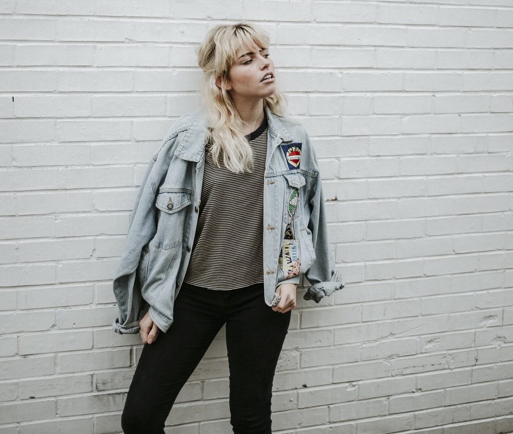 woman in blue denim jacket and black pants standing beside gray wall