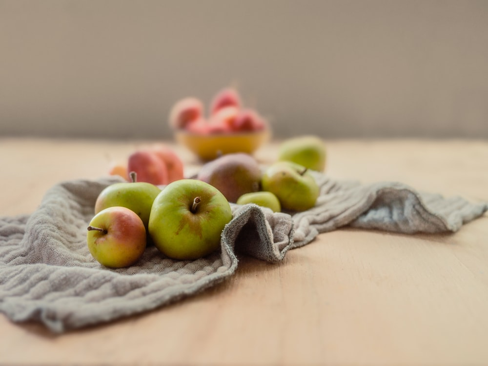 green and red apples on gray textile