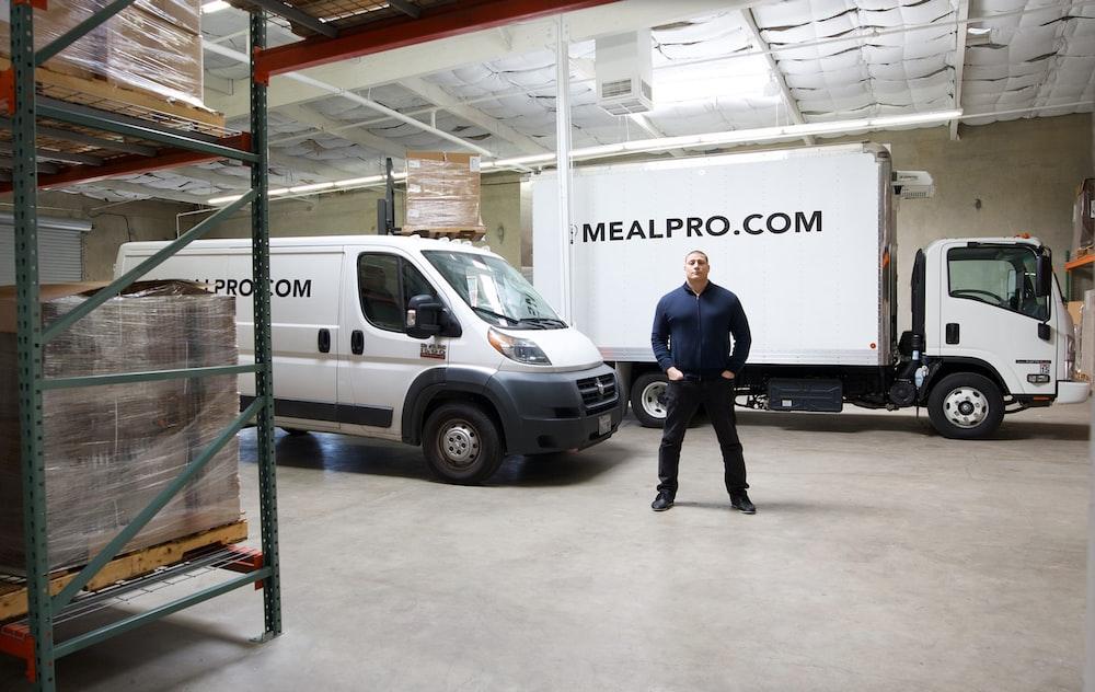 man in blue shirt and black pants standing beside white van