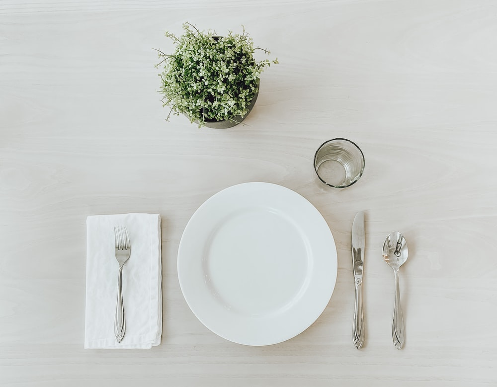 white ceramic plate beside stainless steel fork and bread knife on white table