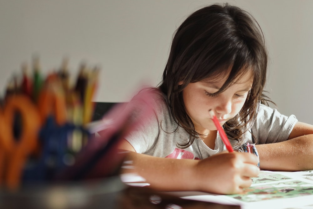 girl in pink t-shirt writing on white paper