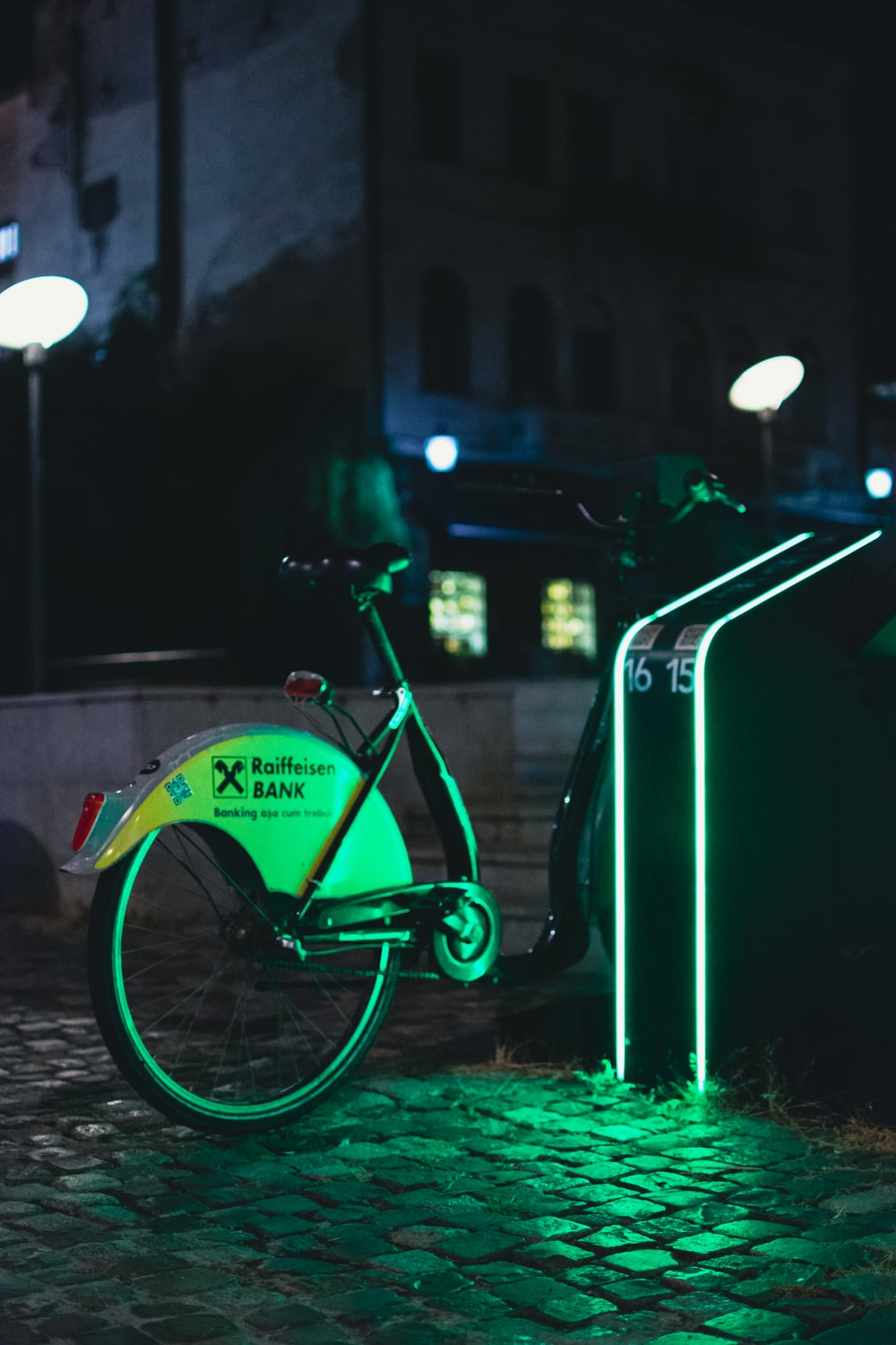 green city bike parked beside green metal post during night time