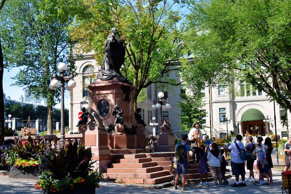 people walking on sidewalk near statue of man riding horse during daytime