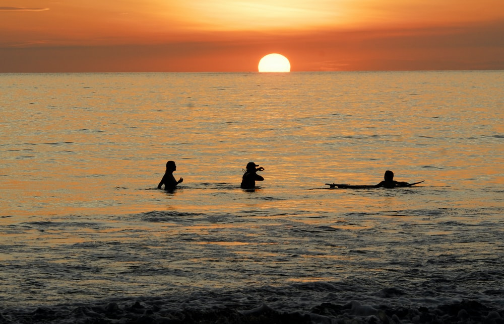 silhouette of people on sea during sunset