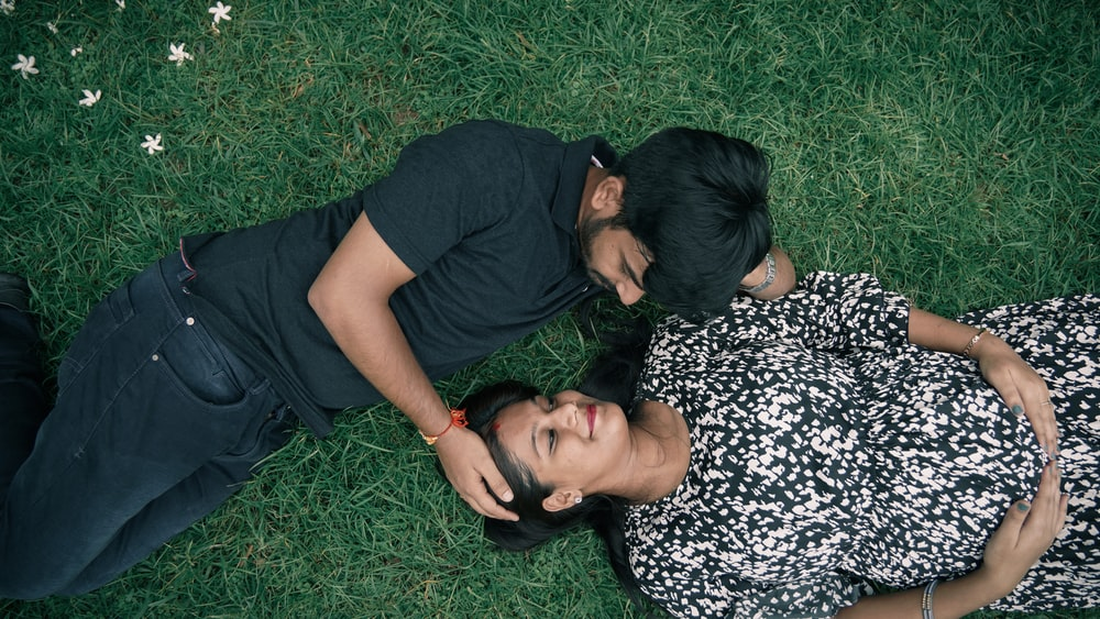 man in black crew neck t-shirt lying on green grass beside woman in black and