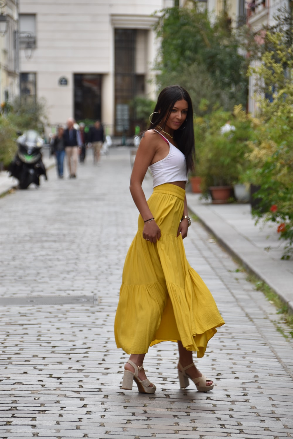 woman in white tank top and yellow skirt walking on street during daytime