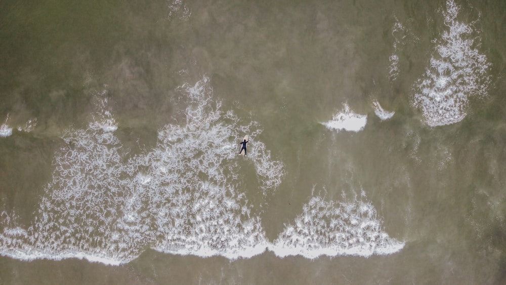 person surfing on sea waves during daytime