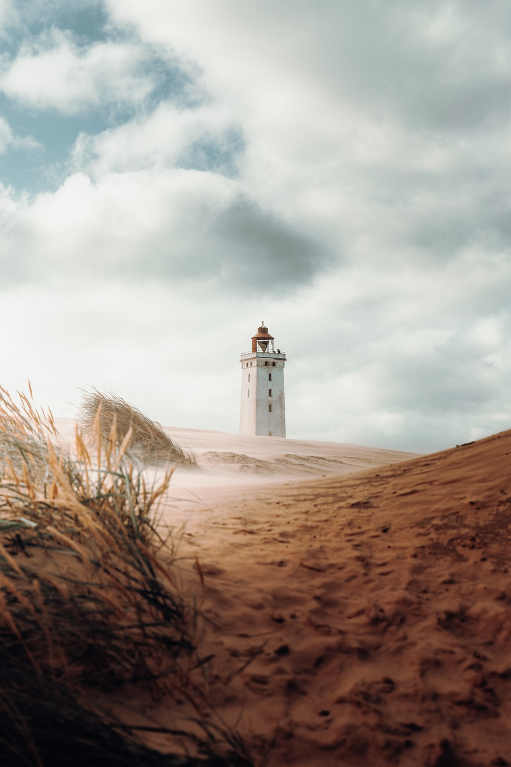 white concrete lighthouse on brown sand under white clouds during daytime