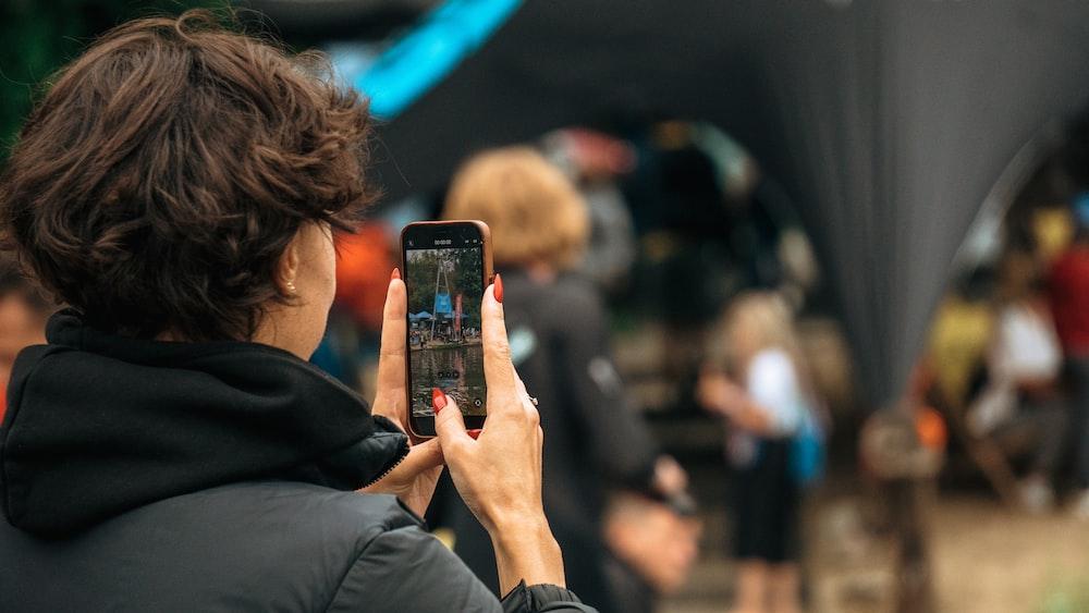 woman in black jacket holding black smartphone