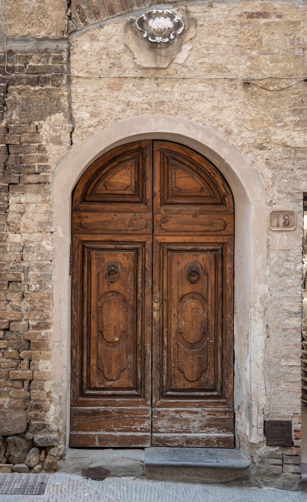 brown wooden door on gray concrete wall