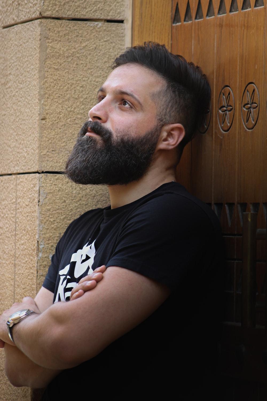 man in black crew neck t-shirt sitting beside brown wooden door