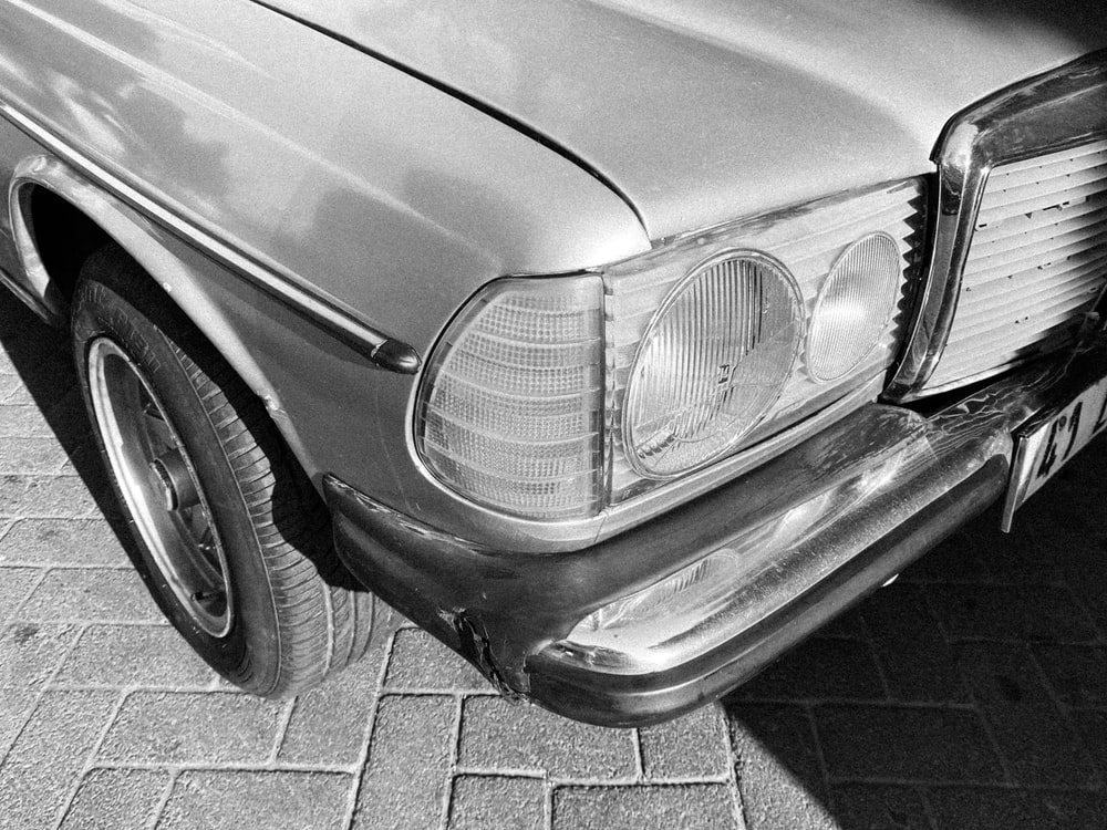 grayscale photo of car on brick floor