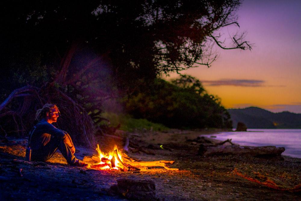 man sitting on ground near bonfire during night time