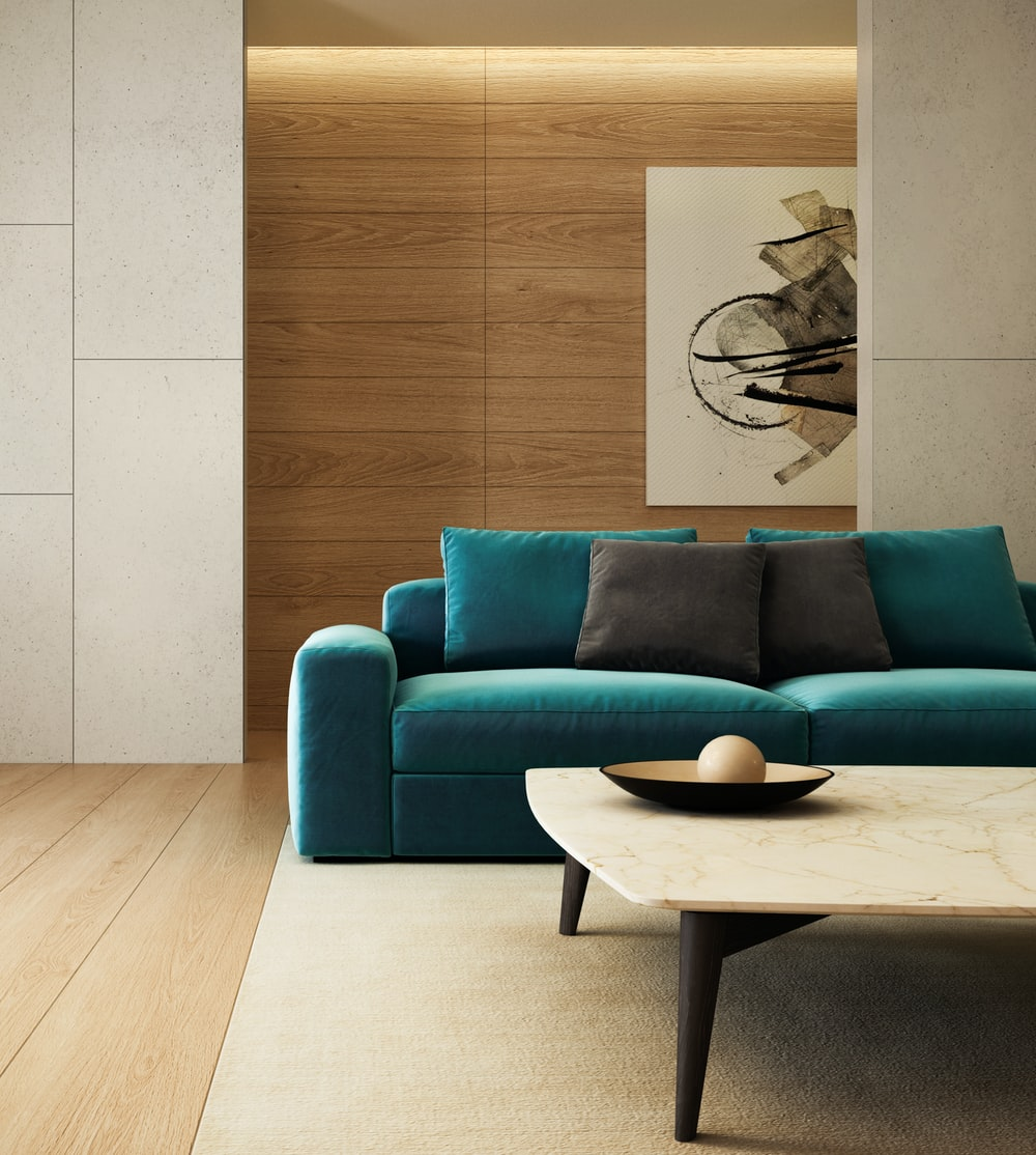 blue sofa beside brown wooden table