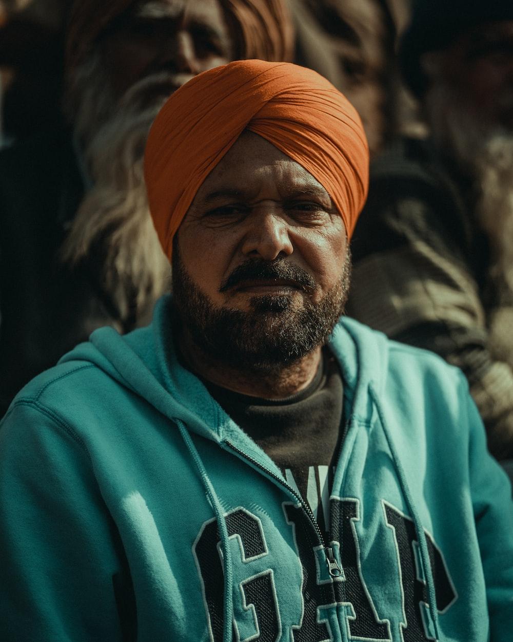 man in teal hoodie wearing orange knit cap