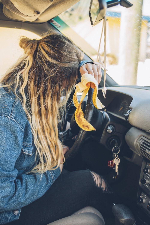 woman in blue denim jacket driving car