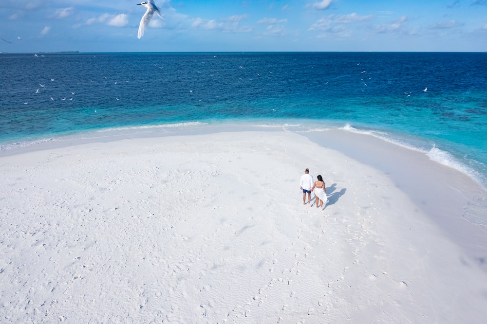 2 person in white shirt and black pants walking on white sand beach during daytime