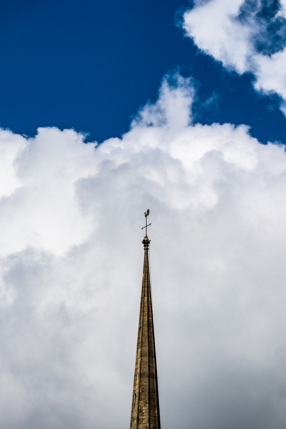 brown tower under blue sky and white clouds during daytime