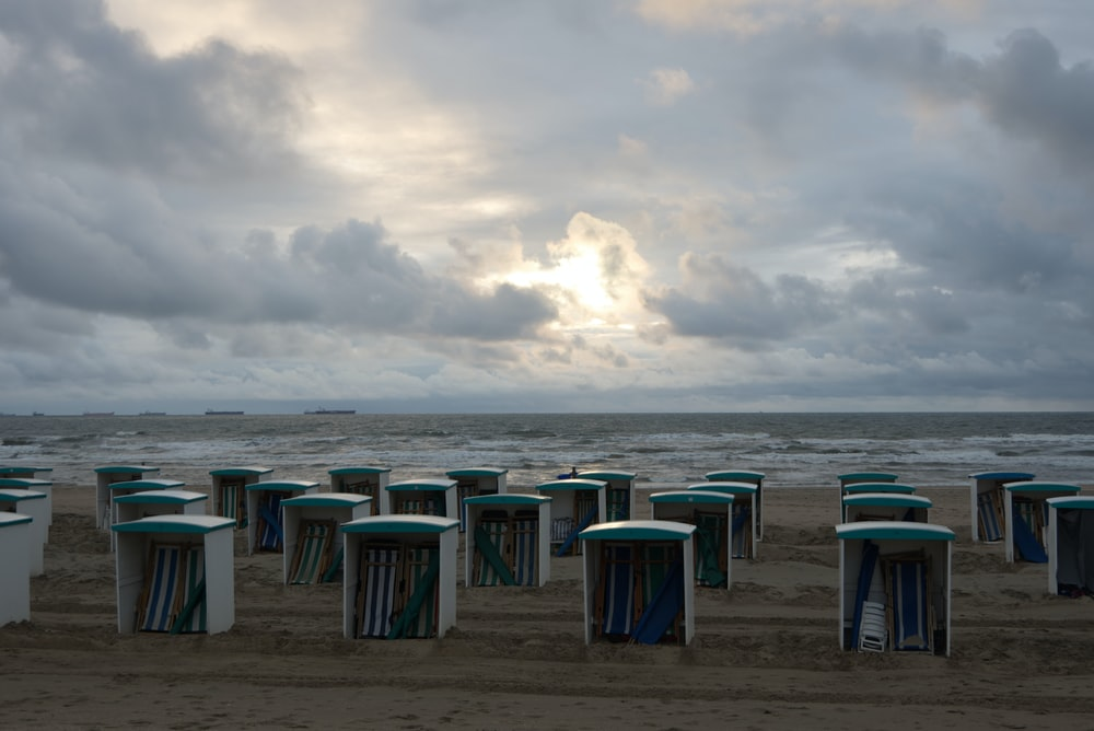 green and blue trash bins on beach under cloudy sky during daytime